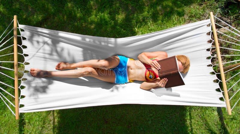 Mädchen liest ein Buch in der Hängematte lizenzfreie stockbilder