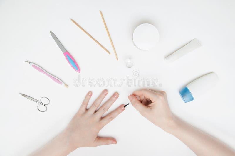 Mädchen macht sich eine Maniküre auf einer weißen Tabelle Nahaufnahme lizenzfreie stockbilder