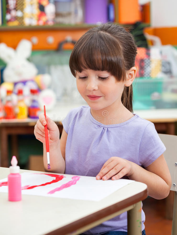 Mädchen-Malerei am Schreibtisch in Art Class lizenzfreie stockbilder