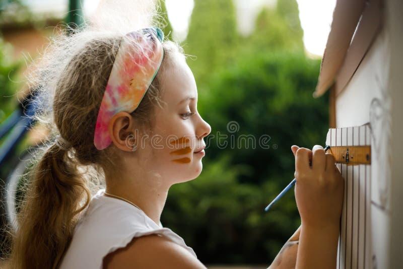 Mädchen malt ein Papphaus am Sommertag, im Freien lizenzfreies stockfoto