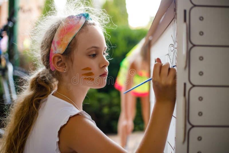 Mädchen malt ein Papphaus am Sommertag, im Freien stockbild