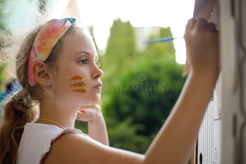 Mädchen malt ein Papphaus am Sommertag, im Freien stockbilder
