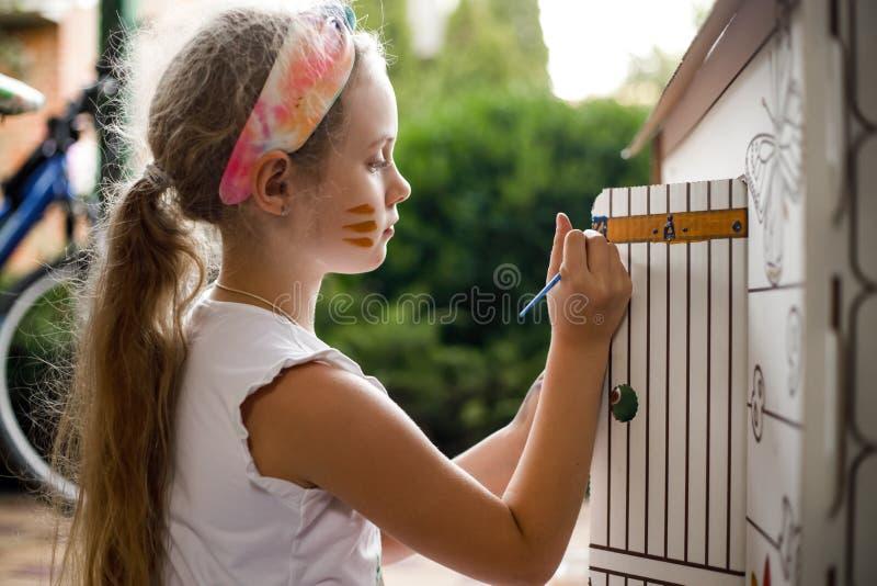 Mädchen malt ein Papphaus am Sommertag, im Freien stockfoto