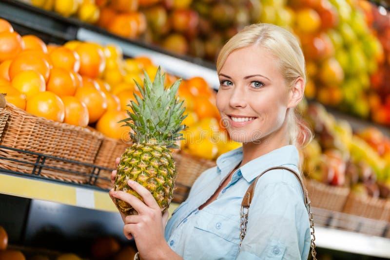 Mädchen am Markt, der Früchte wählt, übergibt Ananas stockbild