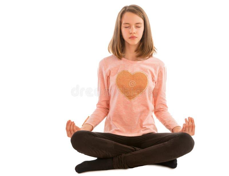Mädchen meditiert beim Sitzen im Lotussitz stockbilder