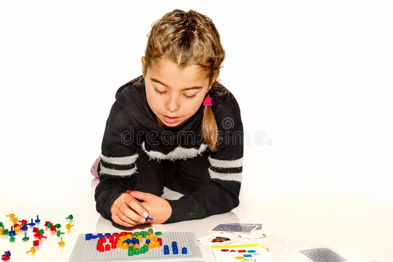 Mädchen mit acht Jährigen, das mit Brettspiel auf Weiß spielt lizenzfreie stockfotografie