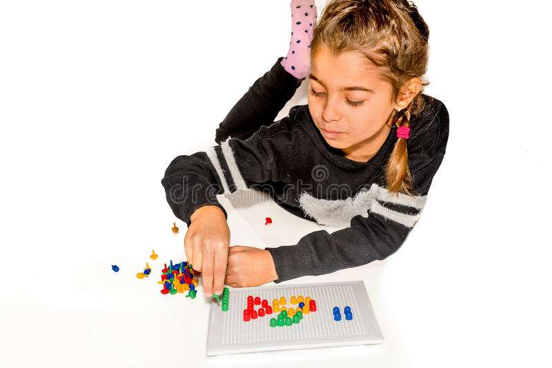 Mädchen mit acht Jährigen, das mit dem Brettspiel lokalisiert auf Weiß spielt stockbilder