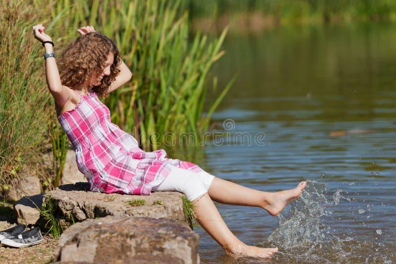 Mädchen mit Arme angehobenem Sitzen auf Felsen während Spritzwasser stockbild