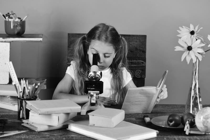 Mädchen mit aufmerksamem Gesicht untersucht Mikroskop Elemente dieses Bildes geliefert von der NASA lizenzfreie stockbilder
