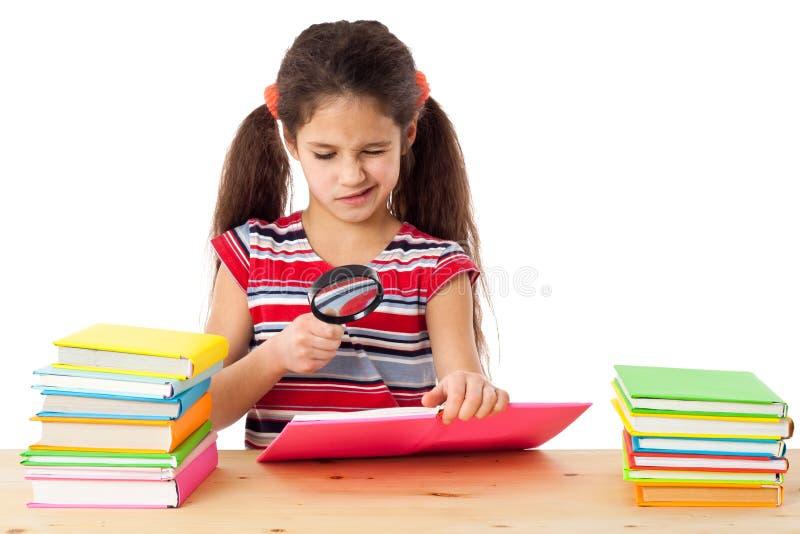Mädchen mit Büchern und Vergrößerungsglas stockfotografie