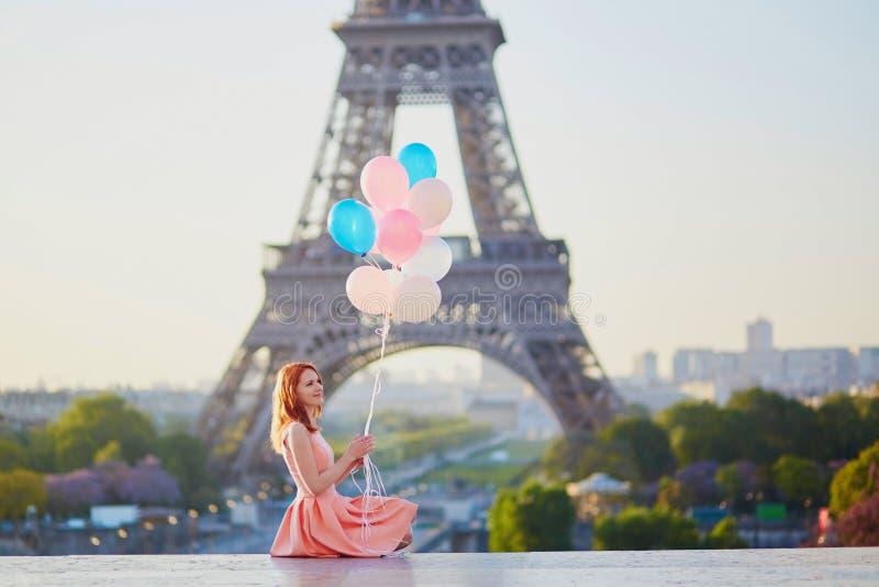 Mädchen mit Bündel Ballonen vor dem Eiffelturm in Paris stockbild