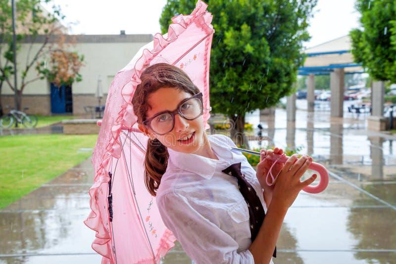 Mädchen mit Bindung und großen Gläsern steht unter rosa Regenschirm lizenzfreies stockbild