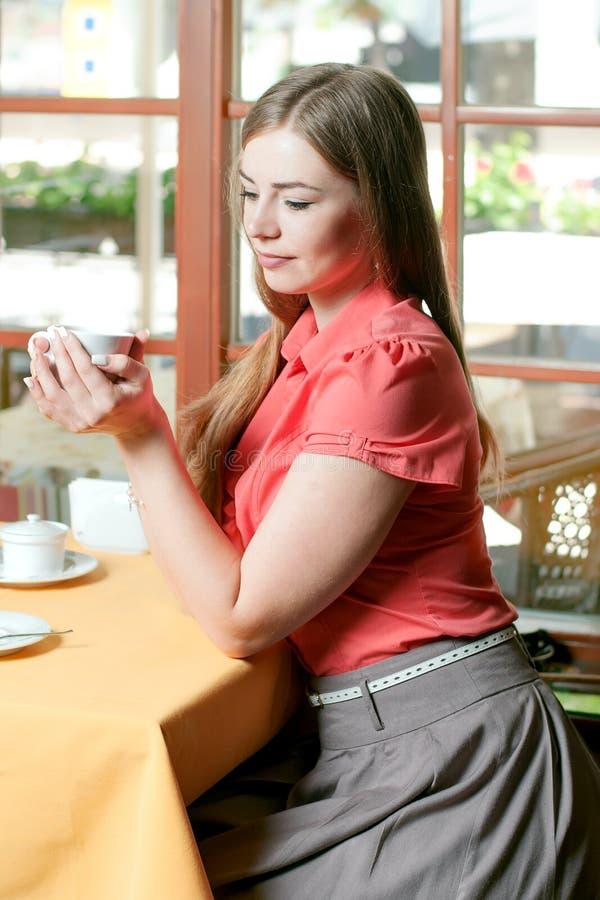 Mädchen mit blauen Augen kleidete in trinkendem Kaffee der roten Bluse in einem r an stockbild