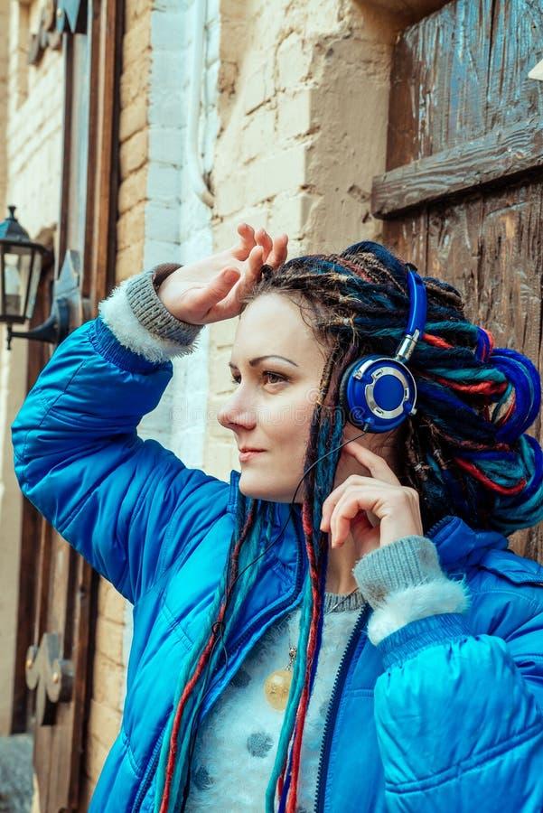 Mädchen mit blauen Dreadlocks hörend Musik auf Kopfhörern lizenzfreies stockbild