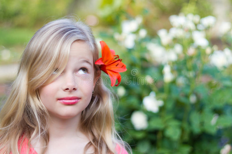 Mädchen mit Blume im Haar lizenzfreie stockbilder