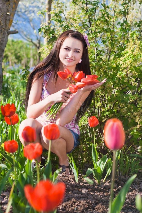 Mädchen mit Blumen im Garten lizenzfreie stockbilder