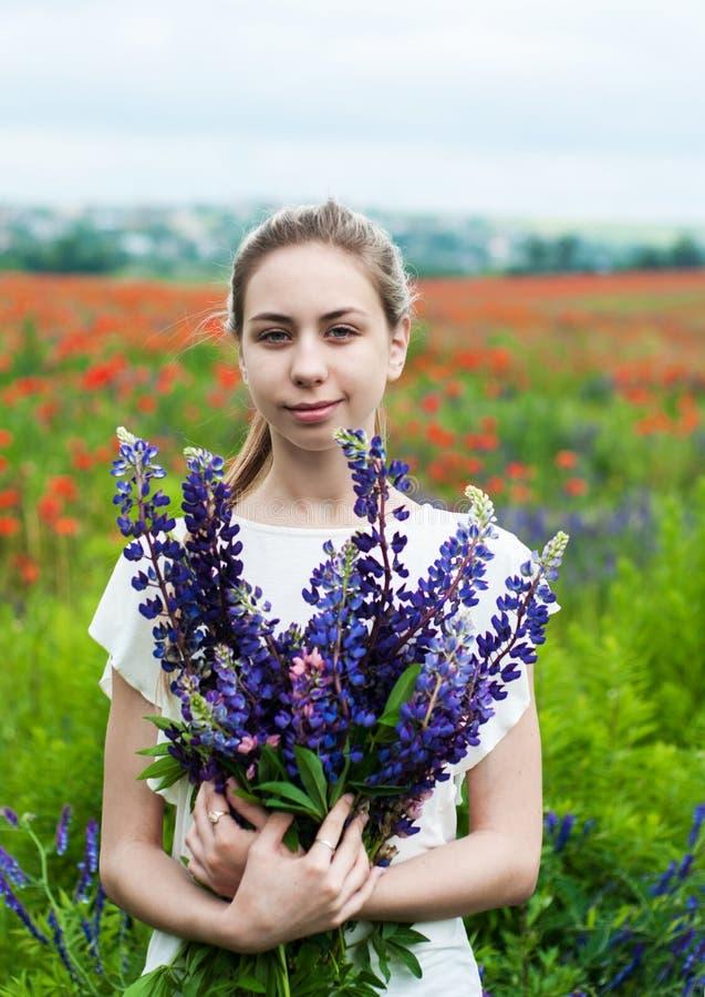 Mädchen mit Blumenstrauß von Lupineblumen stockfotografie