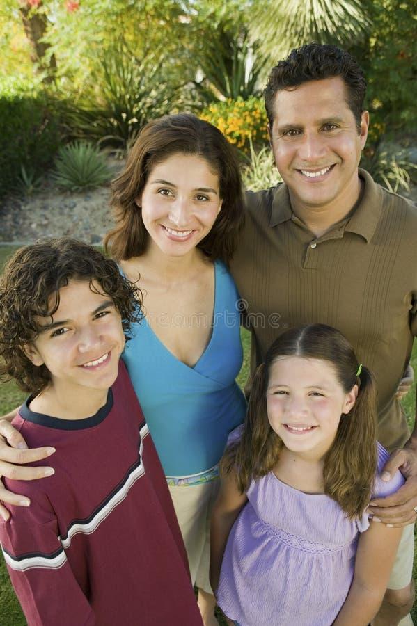 Mädchen (7-9) mit Bruder (13-15) und Eltern draußen erhöhte Ansichtporträt. lizenzfreie stockfotos