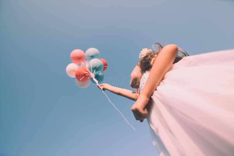 Mädchen mit bunten Ballonen oben im Himmel Niedriger Winkel Retro- Blick stockfoto
