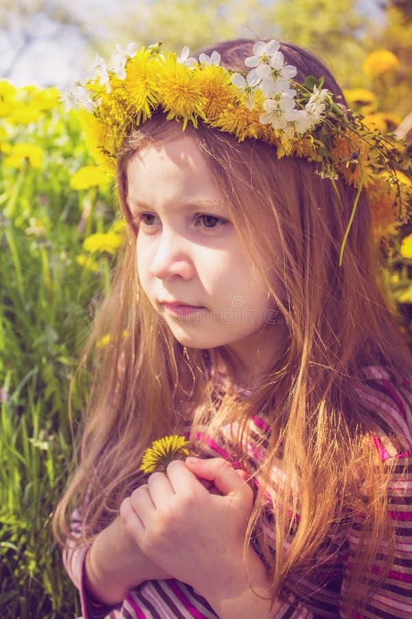 Mädchen mit Chaplet auf Kopf im Garten lizenzfreie stockfotografie