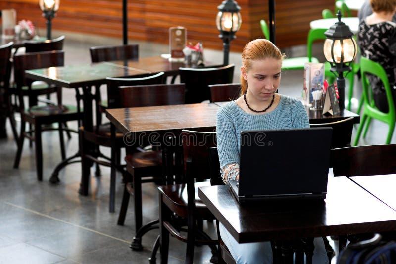 Mädchen mit Computer im Kaffee stockfoto