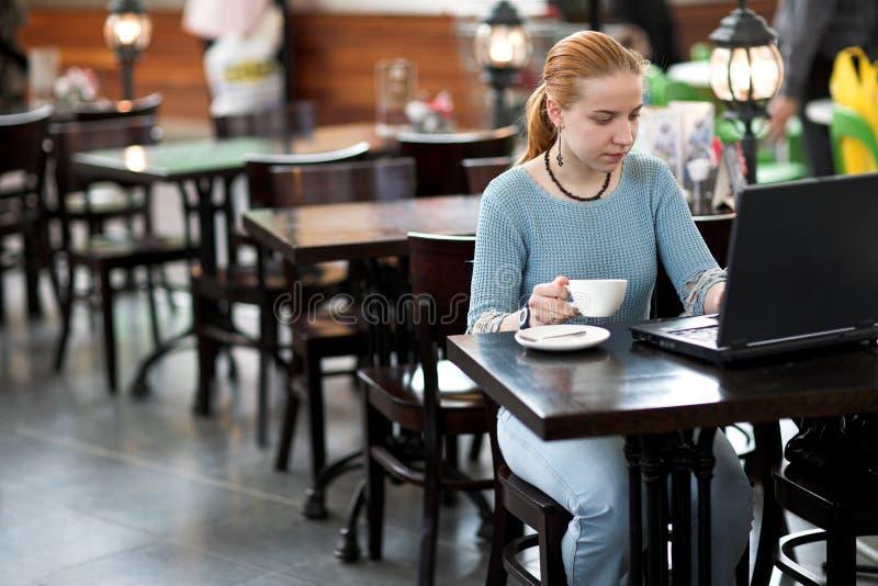 Mädchen mit Computer im Kaffee lizenzfreie stockfotos
