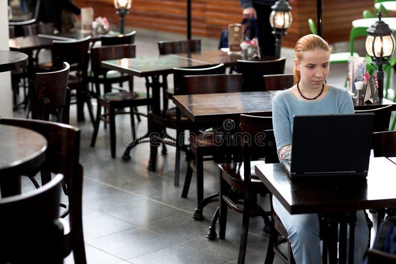 Mädchen mit Computer im Kaffee lizenzfreies stockfoto