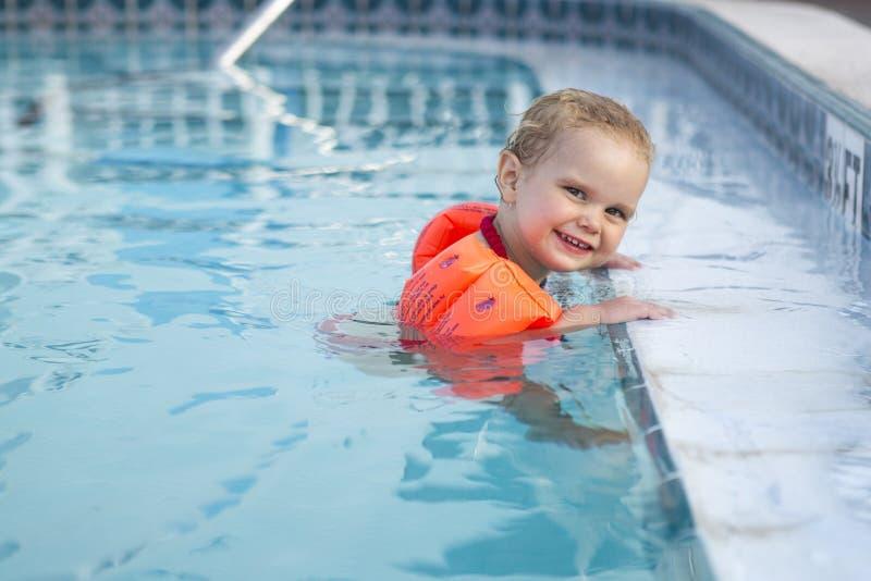 Mädchen mit dem Arm schwimmt ein anhalten zum Rand des Pools lizenzfreie stockbilder