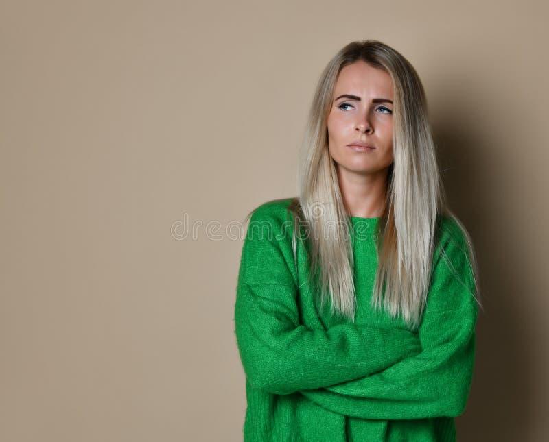 Mädchen mit dem blonden geraden Haar die Stirn runzelnd ihr Gesicht im Verdruß, tragende lose langärmlige grüne Strickjacke,  lizenzfreie stockbilder