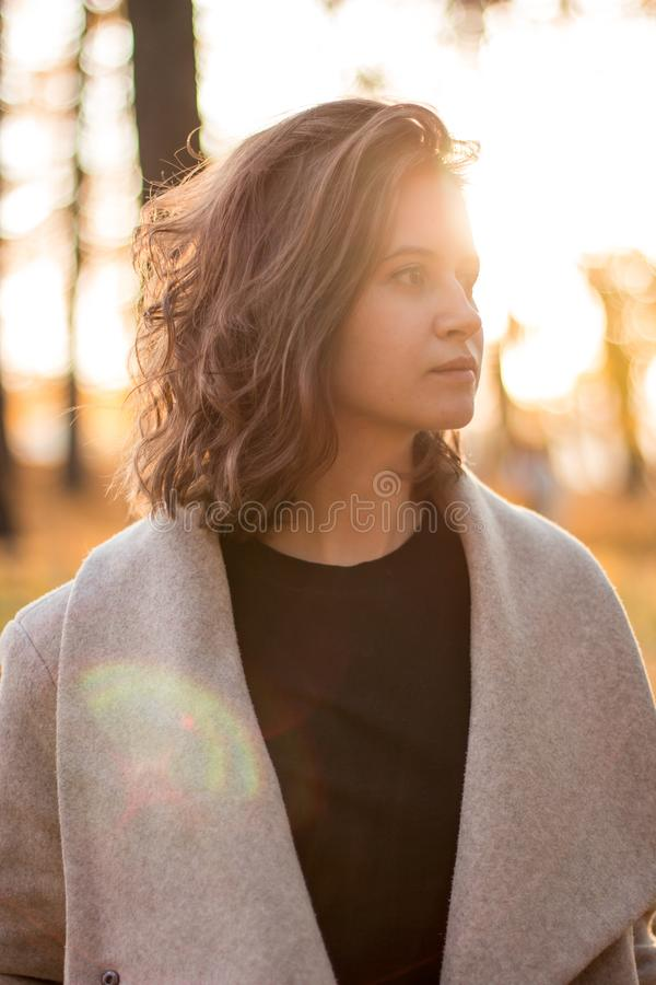 Mädchen mit dem braunen Haar im Herbstwald auf der Hintergrundbeleuchtung stockbilder