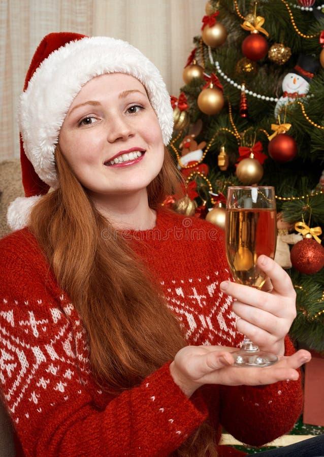 Mädchen mit dem Champagner zu Hause zurechtgemacht als Sankt in der Weihnachtsdekoration Sylvesterabend und Winterurlaubkonzept stockfotografie