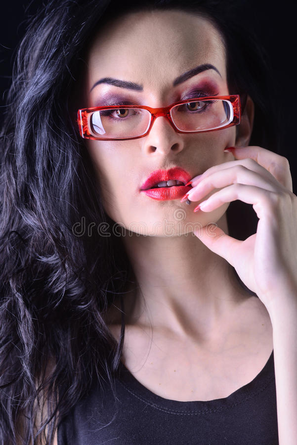 Mädchen mit dem dunklen gelockten Haar, Make-up, rote Gläser stockbild
