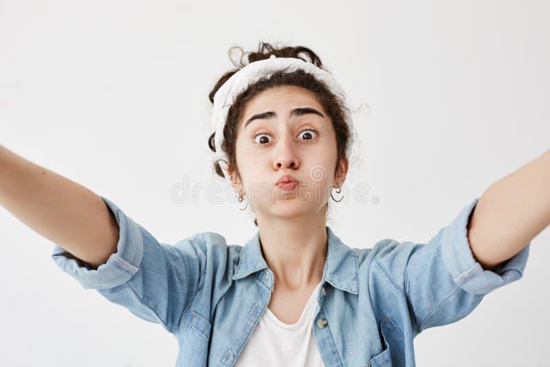 Mädchen mit dem dunklen und gewellten Haar im Brötchen, das Arme zur Kamera, lokalisiert gegen weißen Hintergrund, schmollende Ba lizenzfreie stockfotos