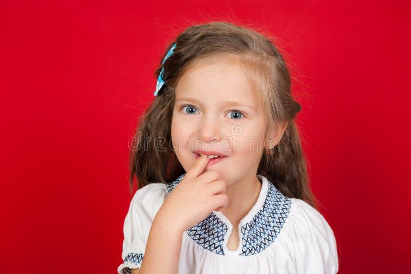Mädchen mit dem Finger im Mund stockbild