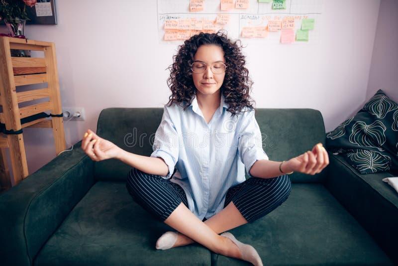 Mädchen mit dem gewellten Haar und den Gläsern, die zu Hause Yoga auf dem Sofa tun lizenzfreies stockfoto