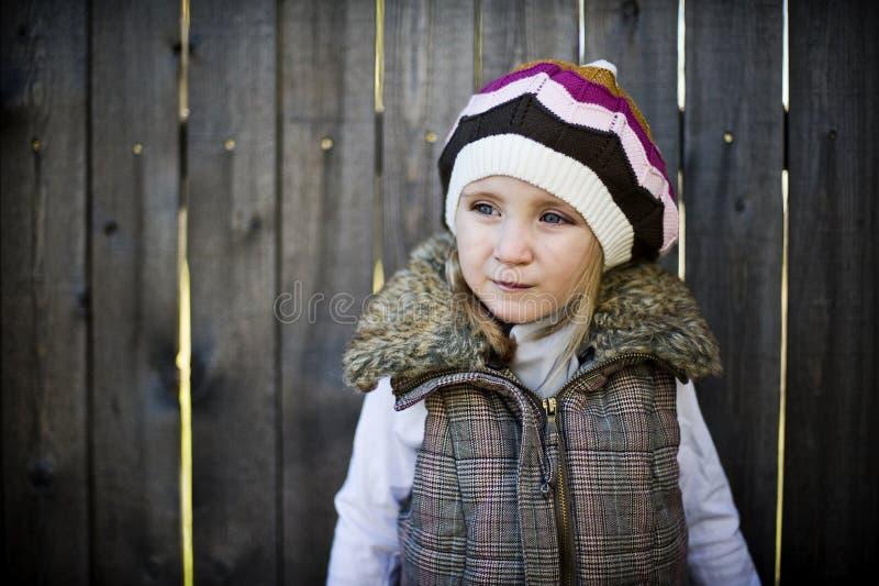 Mädchen mit dem Hut, der vor einem Zaun steht lizenzfreie stockfotografie