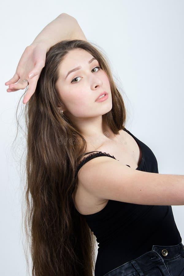 Mädchen mit dem langen dunklen Haar, das auf Stuhl, schwarze Trägershirtjeans aufwirft stockbild