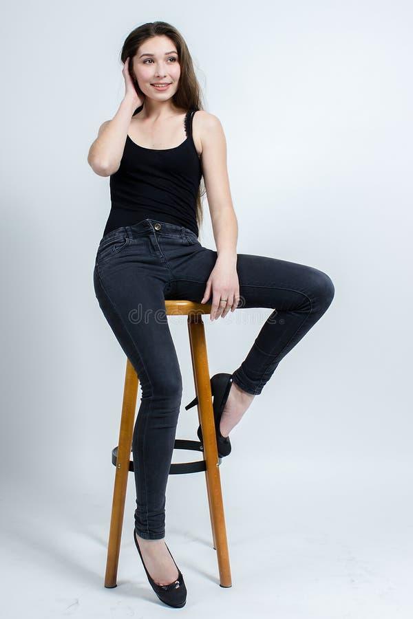 Mädchen mit dem langen dunklen Haar, das auf Stuhl, schwarze Trägershirtjeans aufwirft stockfotografie