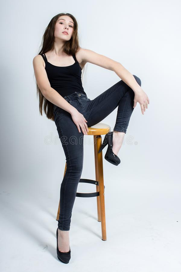 Mädchen mit dem langen dunklen Haar, das auf Stuhl, schwarze Trägershirtjeans aufwirft lizenzfreie stockfotos