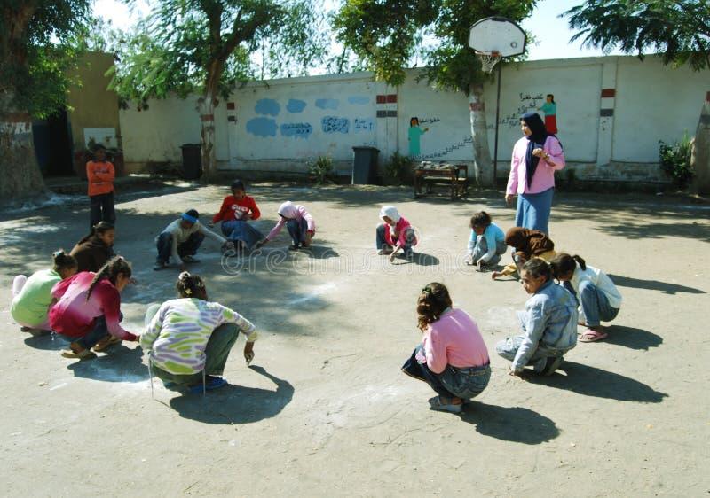 Mädchen mit dem Lehrer, der in der Schule ein Spiel am Spielplatz spielt stockfotos