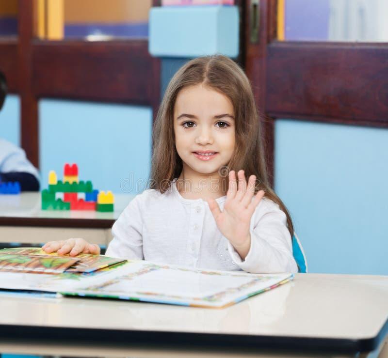Mädchen mit dem Popup- Buch, das am Schreibtisch in der Vorschule wellenartig bewegt lizenzfreie stockbilder