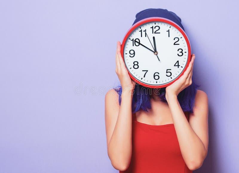 Mädchen mit dem purpurroten Haar und großer Uhr stockbild