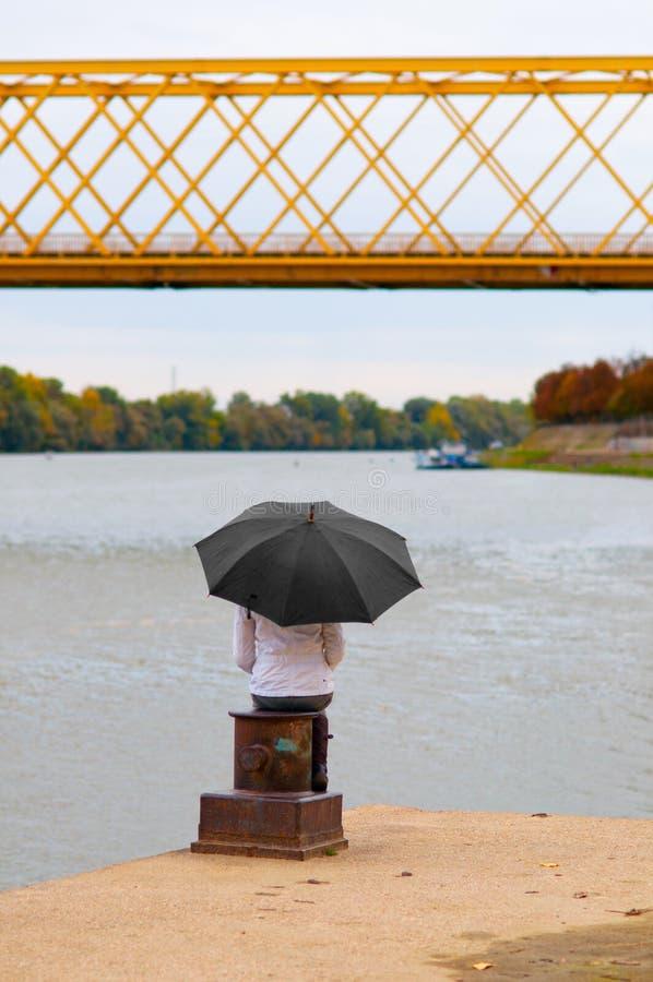 Mädchen mit dem Regenschirm, der auf der Spalte des Docks sitzt stockbilder