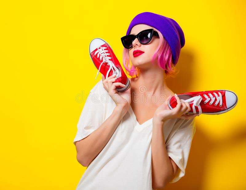 Mädchen mit dem rosa Haar, halten rote Gummiüberschuhe lizenzfreies stockbild