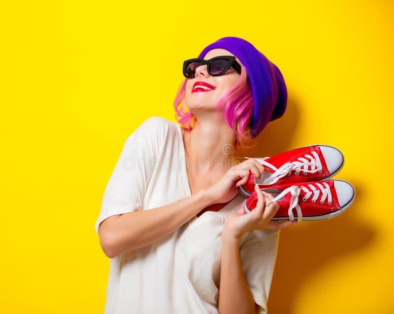 Mädchen mit dem rosa Haar, halten rote Gummiüberschuhe lizenzfreie stockbilder