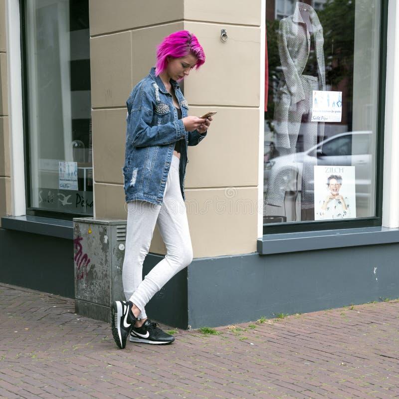 Mädchen mit dem rosa Haar lehnt sich am Speicher mit Mode für Frauen w stockfotografie