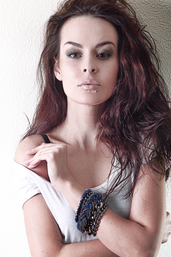 Mädchen mit dem schönen braunen Haar, ein Armband auf ihrem Arm, bloße Schulter, Make-up lizenzfreie stockbilder