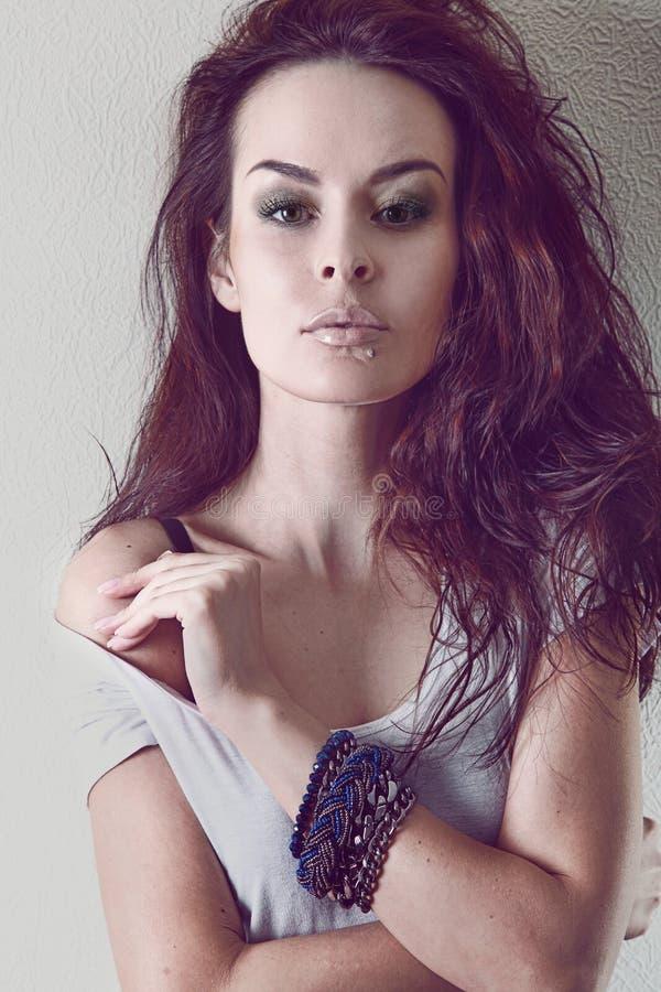 Mädchen mit dem schönen braunen Haar, ein Armband auf ihrem Arm, bloße Schulter, Make-up stockbild