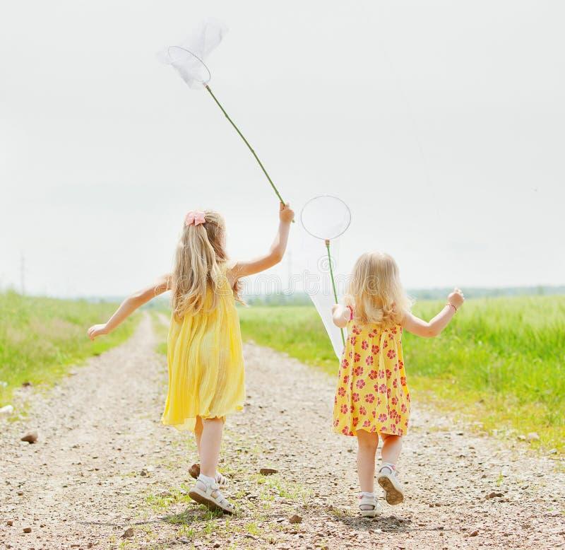 Mädchen mit dem Schmetterlingsnetz, das Spaß hat stockfotos
