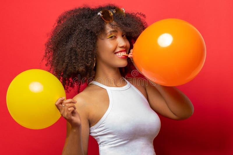 Mädchen mit dem schwarzen gelockten Haar bläst zwei Ballone auf lizenzfreie stockfotografie